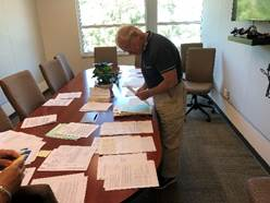 Cold Case homicide retired detective Chuck Gaylor looking through cases spread across a conference room table